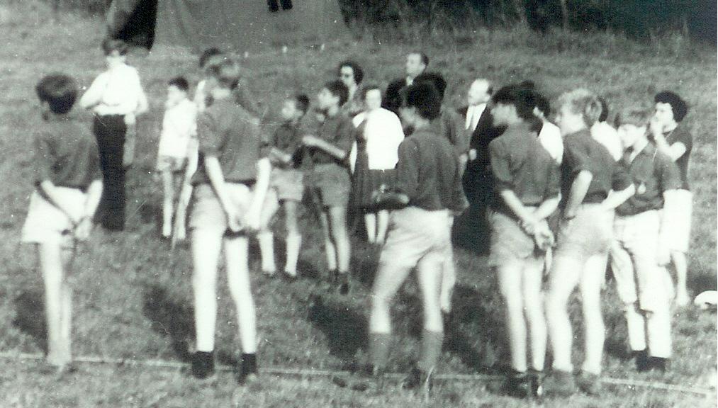 Fig. 5. Août 1967. Grand camp de Forzée. Rassemblement. Deux vues issues de la même photo. À l'arrière-plan, de gauche à droite: l'abbé Jean (AuT), Lapin (CT) et Marmotte (CU). Au premier plan, de dos, la patrouille des Mouettes. De gauche à droite: Hamster (CP), Panda, Kiwi, Tapir, Lièvre, Lynx et Blaireau. À droite, peu visible et tournant le dos aux parents, la patrouille des Sangliers. De gauche à droite: Fauvette (CP) caché par Tapir, Écureuil, Étalon, Puma caché par Lièvre, un scout caché par Lynx et Julo. Entre Kiwi et Tapir, à la droite de Fauvette: Fouine en civil.