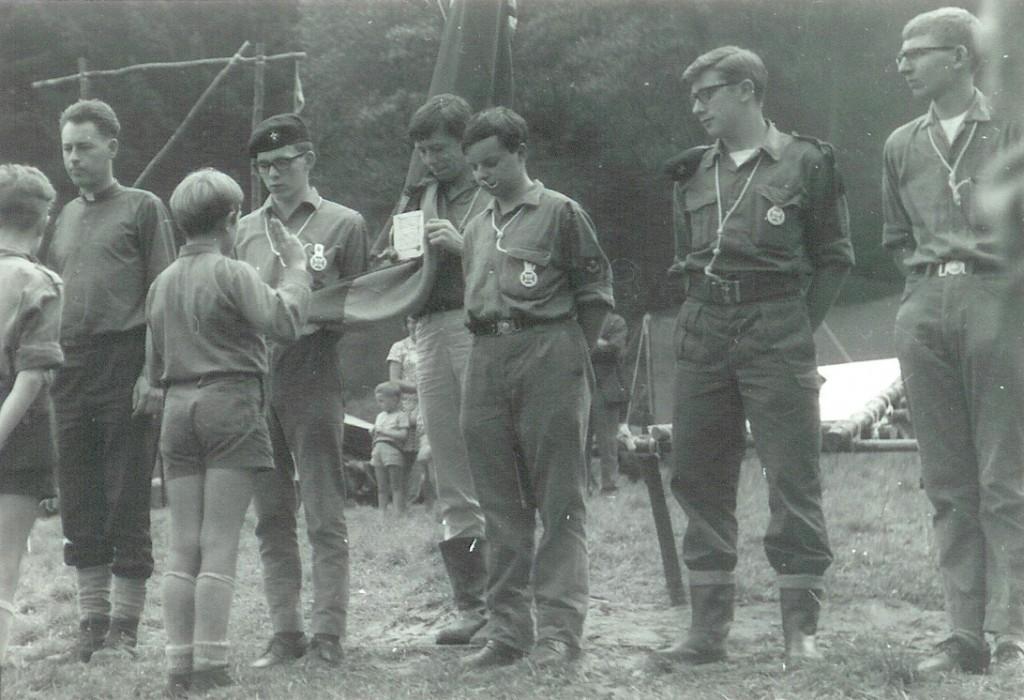 Fig. 9. Août 1968. Grand camp de Brûly-de-Pesche. Promesse de Renard des Mouettes. Deux vues issues de la même photo. À gauche: Okapi (CP des Panthères). Au premier plan, de dos, de gauche à droite : Blaireau (CP des Mouettes), Daim et Renard qui fait sa promesse. Au second plan, de gauche à droite: Faon (AT), l'abbé Jean (AuT), Lapin (CT), Hamster (AT), Phoque (AT), Fouine (AT) et Pécari (AT).